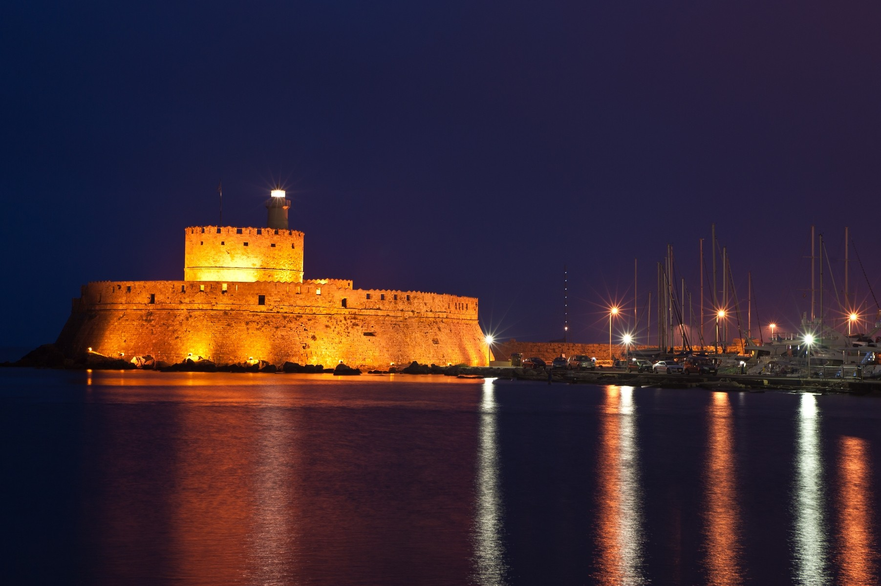 Rhodes island Greece mandraki-of-rhodes-in-the-dodecanese-lighted-at-night 10 must do of Rhodes Activities Greek Recipes Rhodes Holidays Rhodes Island places Rhodes Shops traditional food Rhodes tastes Rhodes restaurants